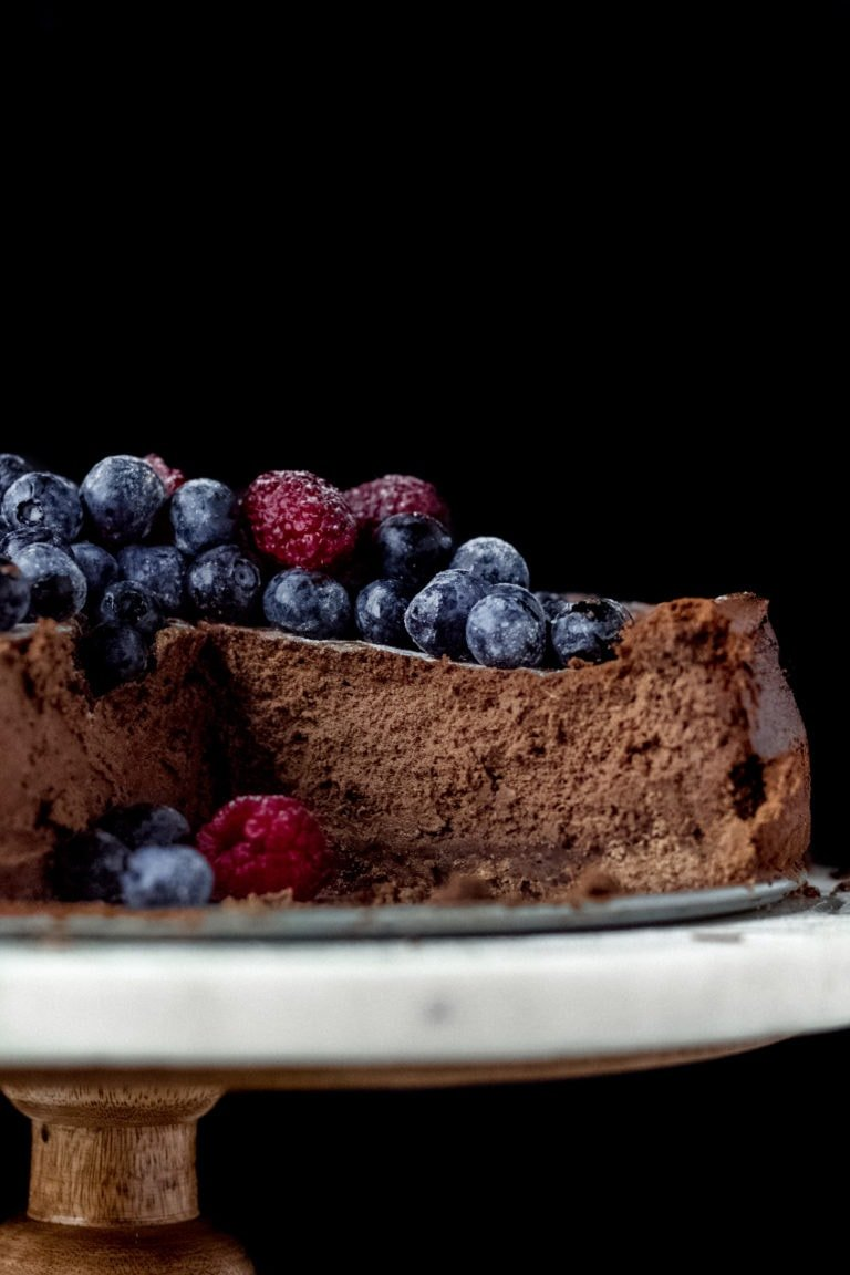 Cut into chocolate cheesecake with berries