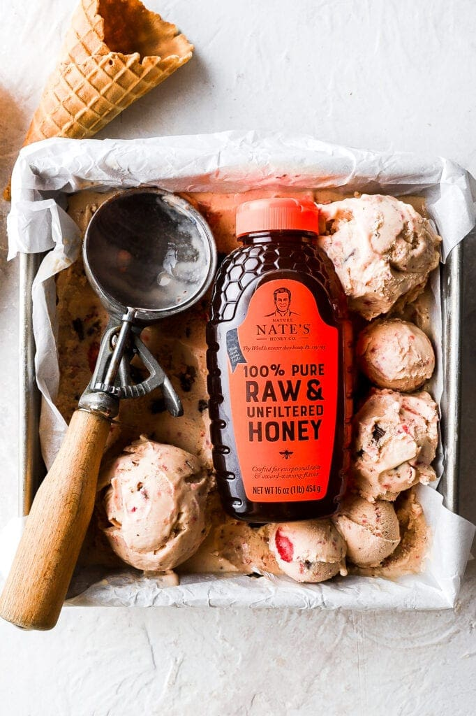 strawberry ice cream scoops with scooper and honey bottle