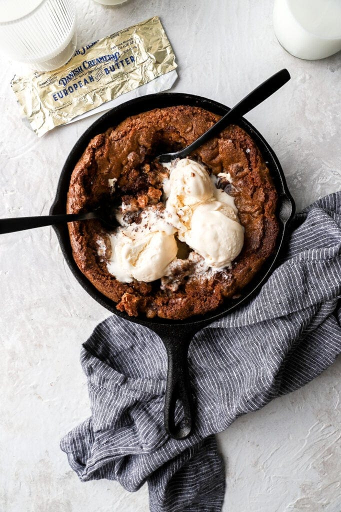 triple chocolate skillet cookie with ice cream, butter wrapper and spoons