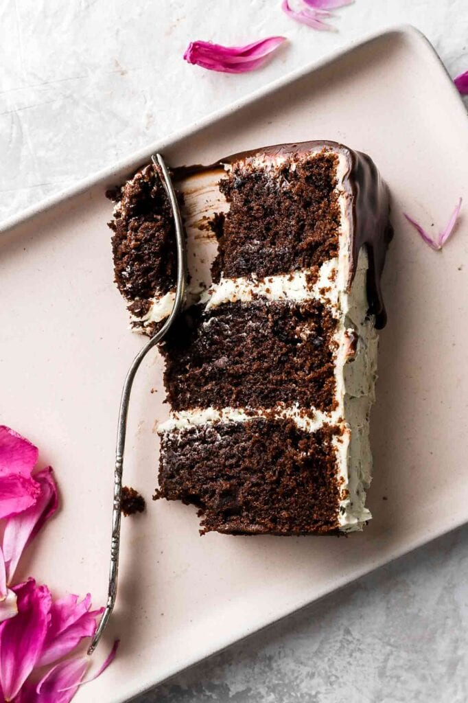 chocolate chip almond cake slice with fork and pink petals
