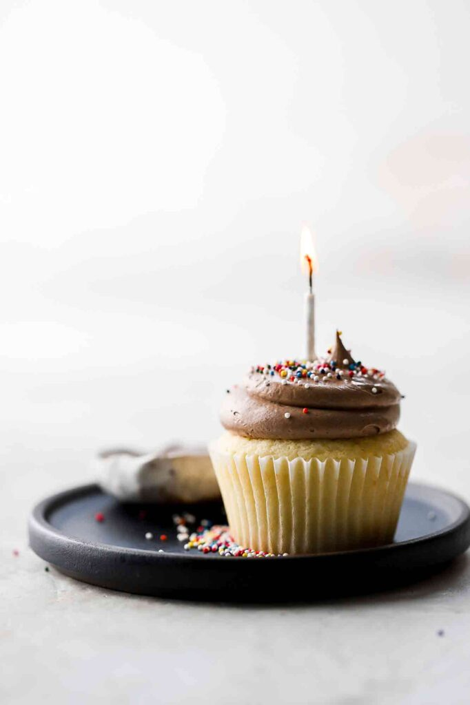 birthday cake cupcakes with lit candle and sprinkles